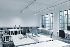 Workplaces in a bright modern loft open space office. Tables are equipped with modern computers; book shelves. Singapore panoramic vector illustration