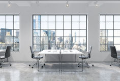 Workplaces in a bright modern loft open space office. Tables are equipped with modern computers. New York panoramic view. A concep Stock Photography