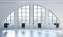 Workplaces in a bright modern open space loft office. White tables and black chairs. New York city view. Royalty Free Stock Images