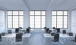 Workplaces in a bright modern open space loft office. White tables equipped with modern laptops and black chairs. White copy space in the panoramic windows. 3D Royalty Free Stock Photos
