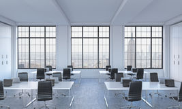 Workplaces in a bright modern open space loft office. White tables equipped with modern laptops and black chairs. New York panoram Royalty Free Stock Image
