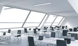 Workplaces in a bright modern open space loft office. White tables equipped by modern laptops and black chairs. White copy space i Stock Photos