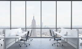 Workplaces in a bright modern open space office. White tables equipped with modern laptops and black chairs. New York in the panor Royalty Free Stock Image