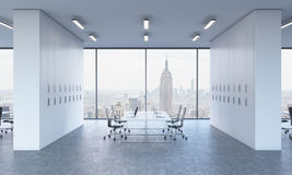 Workplaces in a bright modern open space office. White tables equipped by modern laptops and black chairs. New York panoramic view. 3D rendering Royalty Free Stock Photos