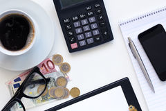 Workplaces, coffee with calculator and money. On a white table Royalty Free Stock Photo