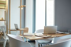 Office for meetings. Workplaces with laptops and notepads and armchairs around in office without people stock image