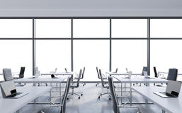 Workplaces in a modern panoramic office, copy space in the windows. Open space. White tables and black leather chairs. Stock Images