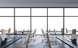 Workplaces in a modern panoramic office, copy space in the windows. Open space. White tables and brown leather chairs. Stock Photo