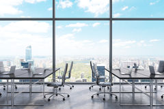 Workplaces in a modern panoramic office, New York city view from the windows. Black tables and black leather chairs. Royalty Free Stock Photo