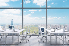 Workplaces in a modern panoramic office, New York city view from the windows. A concept of financial consulting services. 3D rendering Stock Images