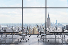 Workplaces in a modern panoramic office, New York city view from the windows. Open space. Black tables and black leather chairs. A Stock Image