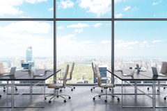 Workplaces in a modern panoramic office, New York city view from the windows. Open space. Black tables and brown leather chairs. Stock Photo