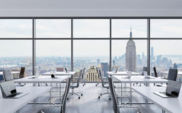 Workplaces in a modern panoramic office, New York city view from the windows. Open space. White tables and black leather chairs. Royalty Free Stock Photos