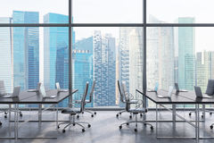 Workplaces in a modern panoramic office, Singapore city view from the windows. Open space. Black tables and black leather chairs. Stock Photos