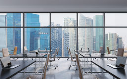 Workplaces in a modern panoramic office, Singapore city view from the windows. Open space. Black tables and brown leather chairs. Royalty Free Stock Images