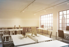 Workplaces in a sunset loft open space office. Tables are equipped with computers; book shelves. New York panoramic view. A concep Royalty Free Stock Images