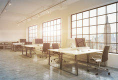Workplaces in a sunset loft open space office. Tables are equipped with computers; book shelves. New York panoramic view. A concep Stock Image