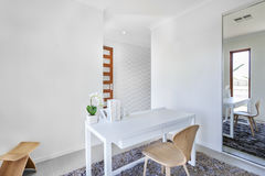 Workroom with white walls and a table with simple decoration Stock Photo
