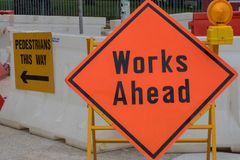 Works Ahead sign in the red plate stands in front of construction site stock images