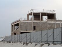 Works on the construction of an apartment house. Behind the fence is the site for the construction of a residential individual house stock photo