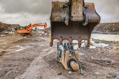 Works in the construction of a road extracting stone in a hard day of winter workDetail of a shovel and a hammer of an excavator royalty free stock photography