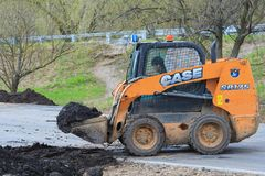Works on the development of the park. Moscow, Russia, april 2018: Works on the development of the park area. Skid steer loader transports black soil editorial stock image