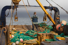 Works on fishing trawler. Filming preparation of trawl to throwing Stock Photos