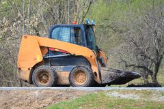 Skid steer loader goes by road stock photo