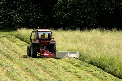 Works on the lawn. Work with the tractor in the grass Stock Image