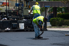 Filling in pot holes on a road Stock Photos