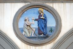 Works of Mercy, Ospedale di San Paolo in Florence. Works of Mercy, glazed terracotta tondo by Andrea della Robbia, located between two arches of the old Ospedale royalty free stock photo
