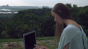 She works at the open air looking at the town with river and beautiful nature. Woman working on the laptop sitting on the hill at the park. Portrait stock video