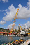 Works in the port of Barcelona. Large floating crane working on repairing a pier of Barcelona Royalty Free Stock Photos