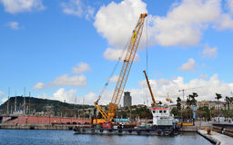 Works in the port of Barcelona. Large floating crane working on repairing a pier of Barcelona Stock Image