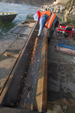Works on the reconstruction of the bridge. Worker finishing metal construction with angle grinder Stock Image
