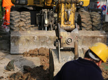 Works on a road construction site with the digger and the worker Stock Photo