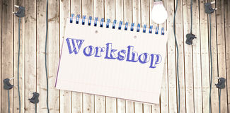 Workshop against notepad on wooden surface Stock Image