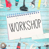 Workshop against tools and notepad on wooden background Royalty Free Stock Images
