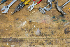 Workshop background, used wooden bench with tools along top border. Workshop background, used wooden bench with tools such as hammer and pliers along top border royalty free stock photography