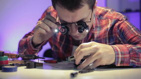 Workshop of electronics and gadgets. The young man in special glasses is sitting at the table and is considering printed board stock video footage