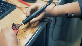 Workshop employee with artificial hands is repairing a microscheme with a soldering tool. 4K