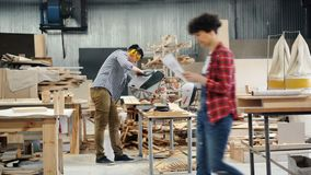 Workshop employee working with circular saw indoors sawing wood. Workshop employee man in casual clothing, protective goggles and headphones is working with stock video