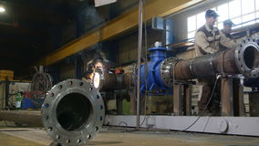 Workshop employee welds pipe construction in oil company stock footage
