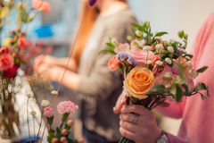 Workshop florist, making bouquets and flower arrangements. Woman collecting a bouquet of roses. Soft focus. Workshop florist, making bouquets and flower Stock Image