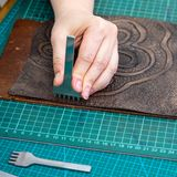 Craftsman punches the decorative item for handbag stock photography