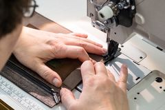 Craftsman stitches the pocket on sewing machine royalty free stock photo