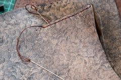 Needles with thread near stitch on leather handbag royalty free stock photos