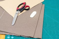 Scissors on textile materials and paper pattern royalty free stock image