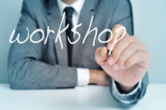 Workshop. Man wearing sitting in a desk writing the word workshop in the foreground royalty free stock photos
