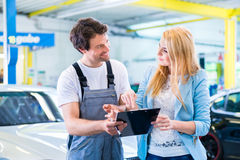 Workshop mechanic handing over car to client Stock Images